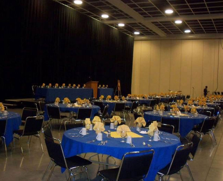 Banquet hall arranged with round tables covered with blue table clothes surrounded by black dining chairs