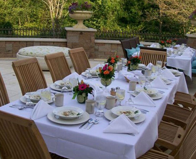 Outdoor patio staged as a wedding reception venue complete with decorated tables and chairs