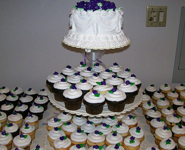 Desert table filled with rows of decorated cupcakes and a cupcake tower